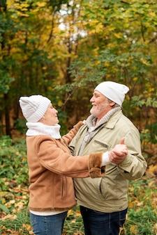Doce casal dançando no parque no outono