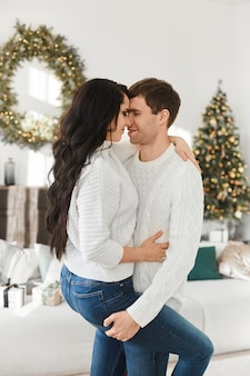 Doce casal de jovens amantes passa a manhã de natal em casa