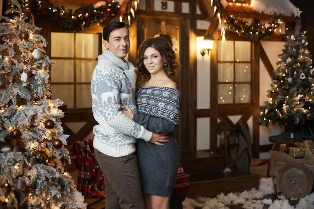 Doce casal elegante com roupas aconchegantes, posando ao lado de uma árvore de natal, perto de sua casa de campo em ...