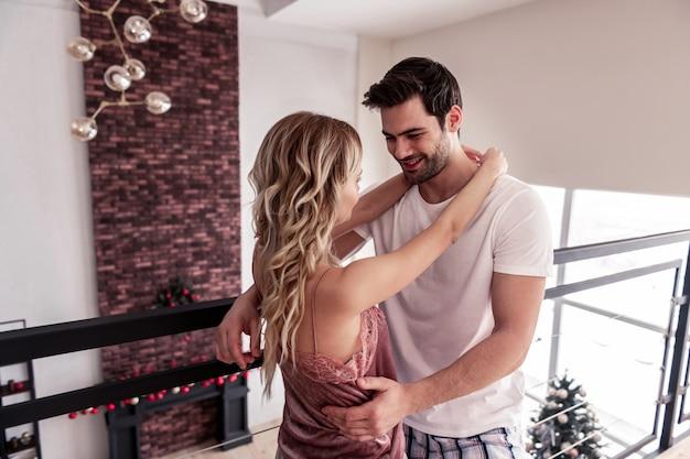 Doce casal. moreno bonito e barbudo em uma camiseta branca parecendo feliz enquanto abraça sua esposa loira e magra de cabelos compridos