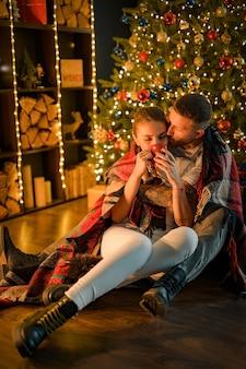 Doce casal sonhador abraçando chocolate quente, tão romântico, no chão em xadrez, festa de inverno