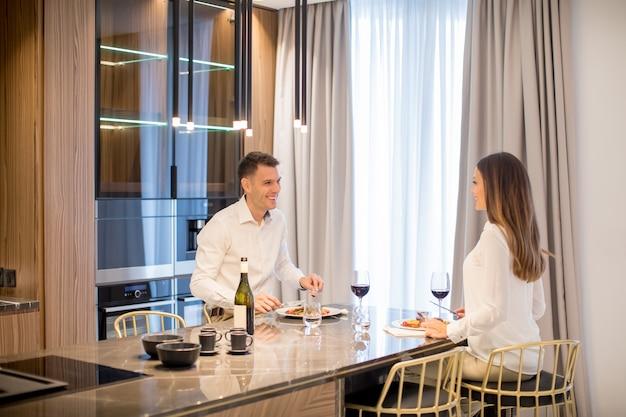 Doce casal tendo um jantar romântico na cozinha de luxo