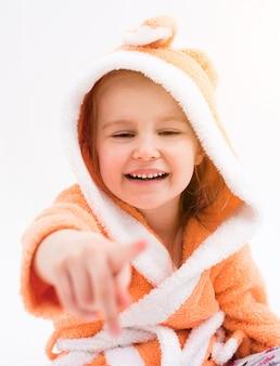 Doce criança apontando algo e rindo