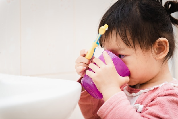 Doce, criança asiática, menininha, escovar, dela, dentes, em, banheiro