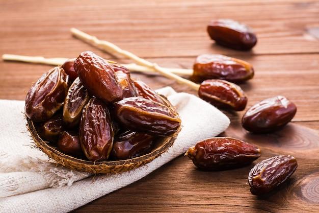 Doce datas secas frutas em uma tigela pequena no guardanapo na mesa de madeira