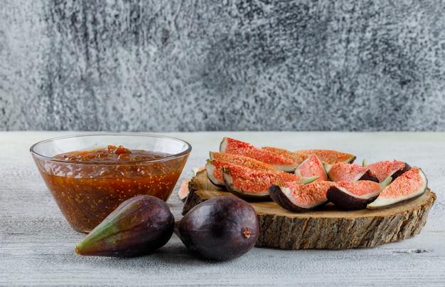 Doce de figo com figos em uma tigela na placa suja e de madeira, vista lateral.