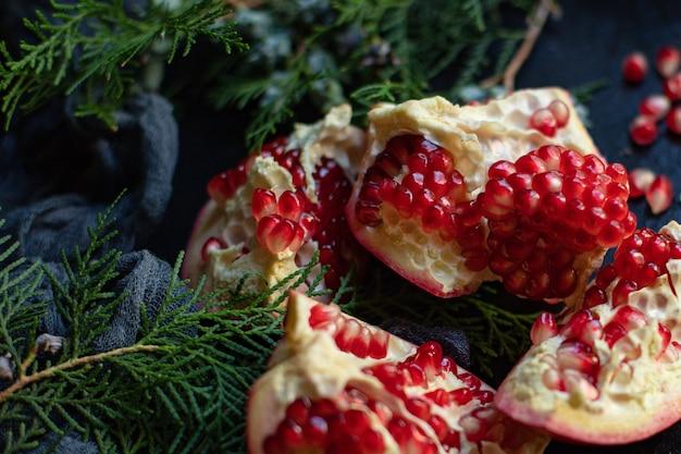 Doce de fruta vermelha de romã na mesa e um galho de árvore de natal verde