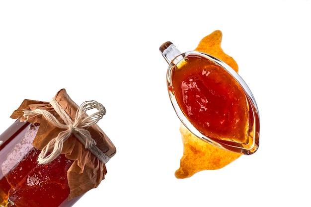 Doce de frutas de cor laranja geléia em uma tigela de vidro e o frasco isolado no fundo branco. vista do topo. postura plana