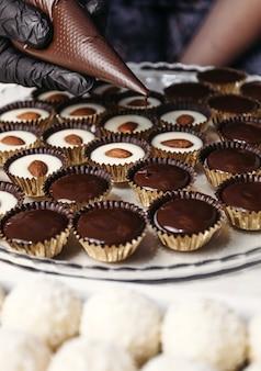 Doce de ganache de chocolate com amêndoas. derramando chocolate, sobremesa caseira.