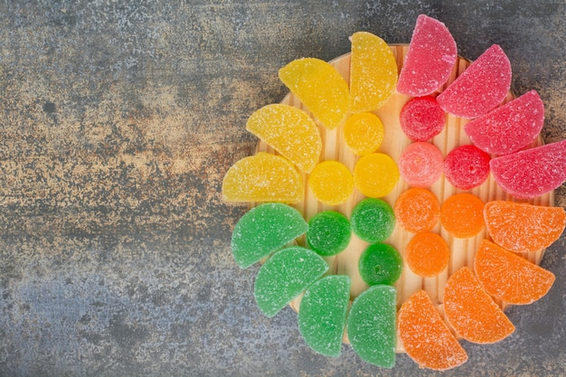 Doce de geleia colorida em prato de madeira