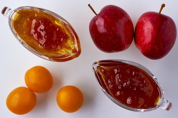 Doce de maçã e ameixa cereja em vidraria e ingredientes em fundo branco. vista do topo. postura plana.