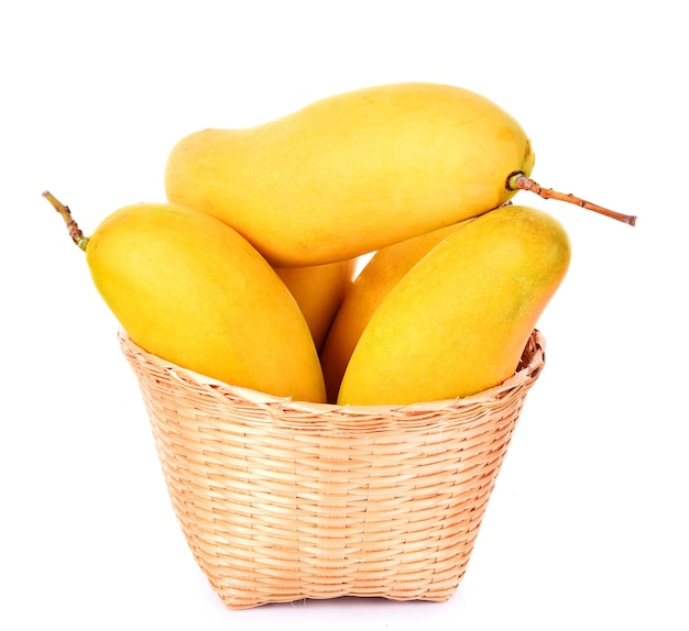Doce de manga amarela na cesta em fundo branco