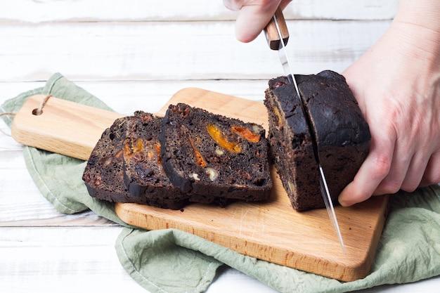 Doce doce de pão preto com ameixas, damascos e nozes cortado com uma faca de cozinha.