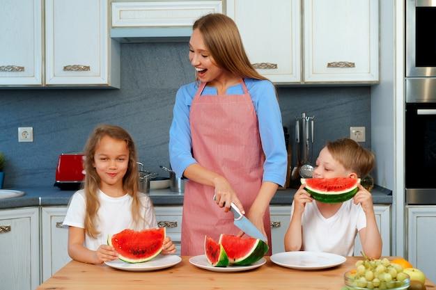 Doce família, mãe e filhos comendo melancia na cozinha se divertindo