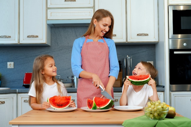Doce família, mãe e filhos comendo melancia na cozinha se divertindo,