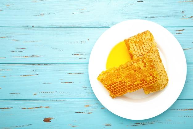 Doce favo de mel no fundo azul, produtos de mel pelo conceito de ingredientes naturais orgânicos