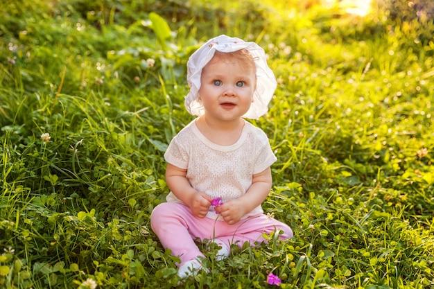 Doce feliz bebê menina sentada na grama no parque, jardim, prado