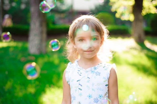 Doce, feliz, sorridente menina de cinco anos deitado em uma grama