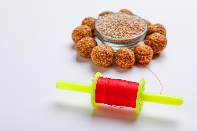 Doce gergelim laddu e semente de gergelim em uma tigela de vidro com fikri para o festival indiano makar sankranti