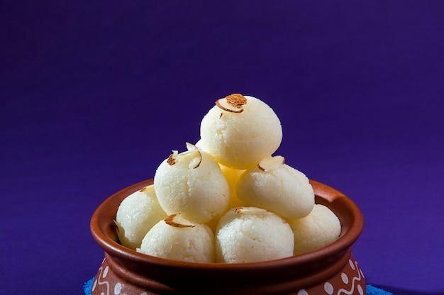 Doce indiano ou sobremesa - rasgulla, famoso doce bengali em tigela de barro com guardanapo azul sobre fundo violeta