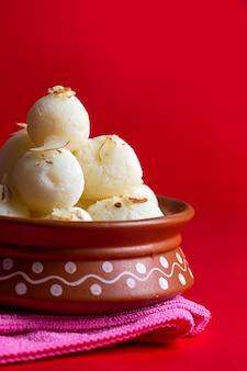 Doce indiano ou sobremesa - rasgulla, famoso doce bengali em tigela de barro com guardanapo sobre fundo vermelho