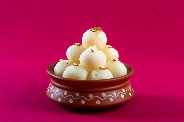 Doce indiano ou sobremesa - rasgulla, famoso doce bengali em tigela de barro em um fundo rosa.