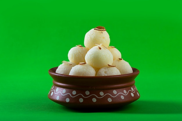 Doce indiano ou sobremesa - rasgulla, famoso doce bengali em tigela de barro sobre fundo verde