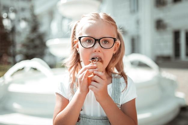 Doce infância. menina séria de óculos comendo sua casquinha de sorvete de chocolate do lado de fora, segurando-a com as duas mãos.