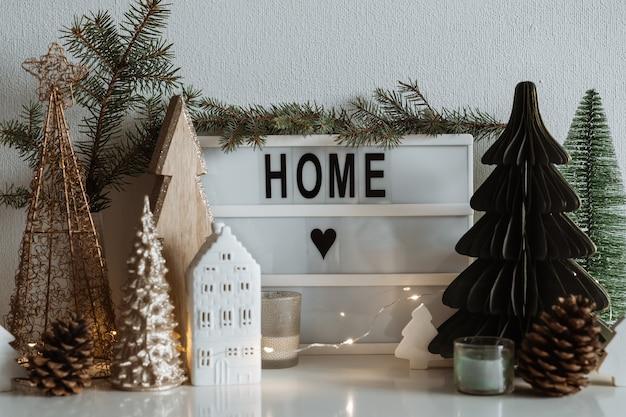Doce lar. casinha de cerâmica de natal, pinheiros de madeira. decorações festivas e modernas.
