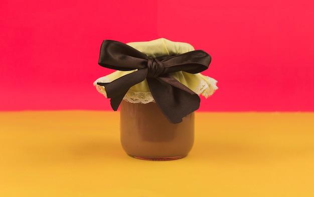 Doce leite brasileiro e geleia no pote isolado em fundo colorido. tendência de pastel de cores frescas.