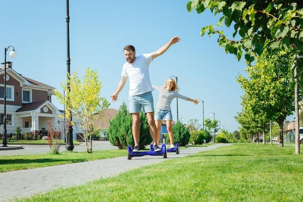 Doce liberdade. homem e mulher alegres e agradáveis em patinetes que se equilibram, seguindo um ao outro e rindo enquanto estendem as mãos