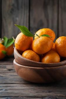 Doce mandarim laranja fresco na mesa de madeira, foco seletivo