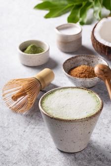 Doce matcha latte chá verde japonês com leite de coco no fundo branco.