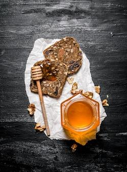 Doce mel em frasco de vidro e pão de frutas com nozes em fundo preto rústico