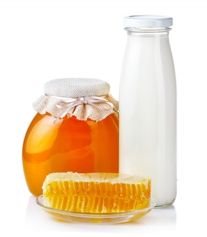 Doce mel em potes de vidro com favos de mel e garrafa de leite isolado