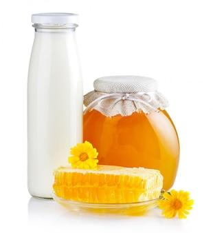 Doce mel em potes de vidro com flores, favos de mel e garrafa de leite isolado