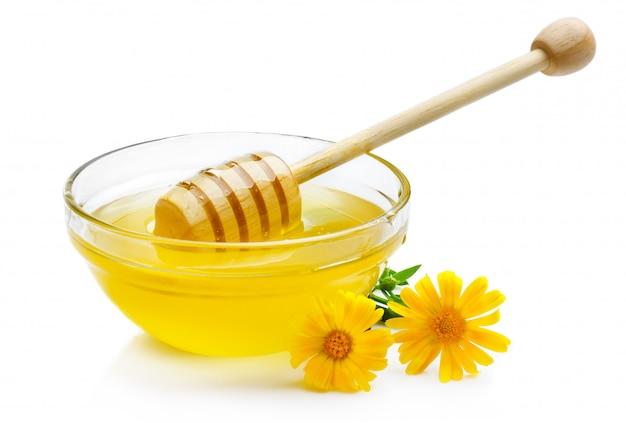 Doce mel na tigela de vidro isolada com dipper de madeira