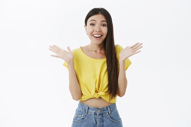 Doce menina asiática encantada com longos cabelos escuros em uma camiseta amarela cortada, segurando as mãos e sorrindo