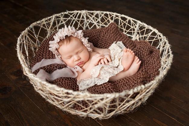 Doce menina bebê recém-nascido dorme na cesta.