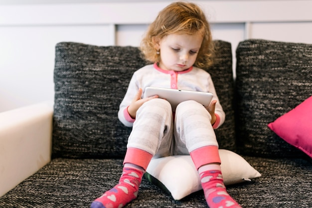 Doce menina com tablet no sofá