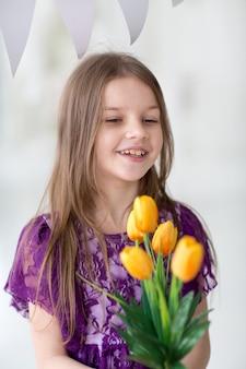 Doce menina de cabelos escuros no vestido roxo em estúdio com tulipas amarelas