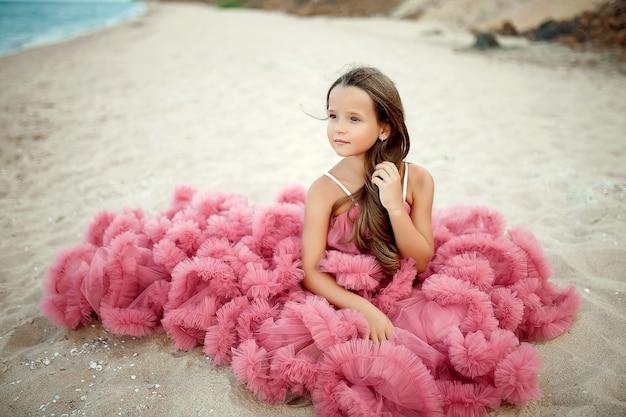 Doce menina de vestido rosa na praia