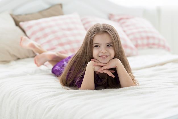 Doce menina de vestido roxo na cama com coxins