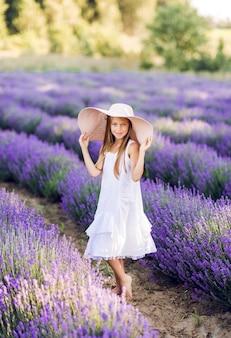 Doce menina em um campo de lavanda. um grande chapéu e um vestido branco sobre ele.
