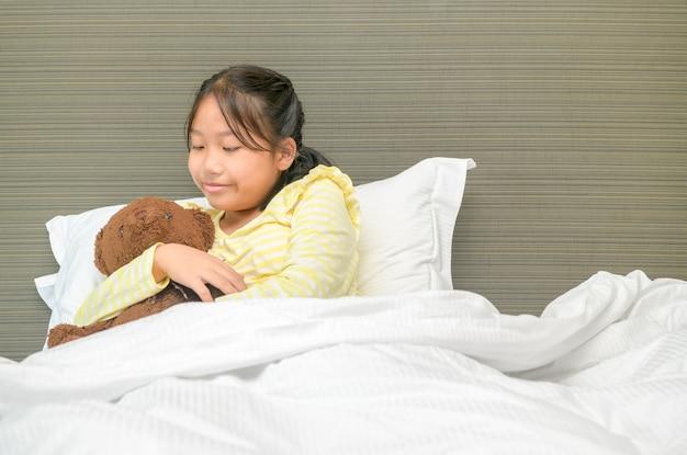 Doce menina está abraçando um ursinho de pelúcia, olhando para o urso e sorrindo enquanto está deitada em sua cama em casa