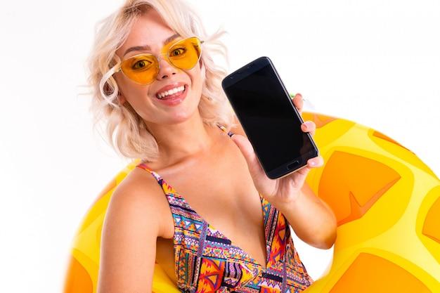 Doce menina loira atraente em um maiô sexy em óculos de sol detém um smartphone com maquete com um abacaxi círculo de natação