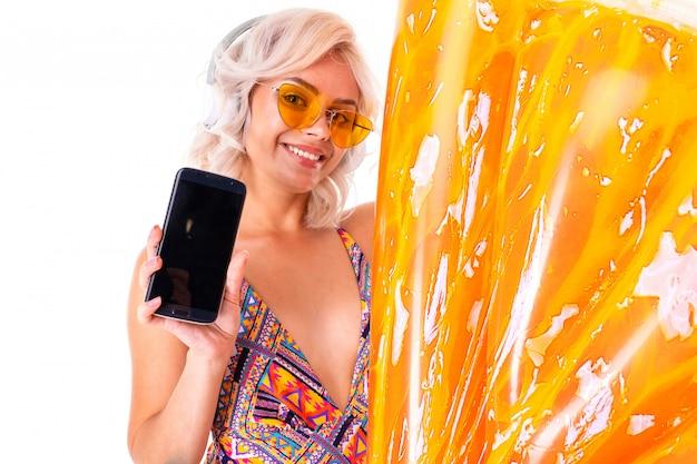 Doce menina loira de biquíni em óculos de sol detém um telefone com maquete com um abacaxi círculo de natação