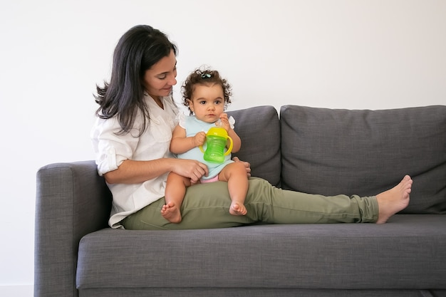 Doce menina sentada no colo das mães e bebendo água da garrafa. copie o espaço. conceito de paternidade e infância