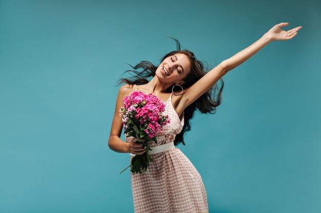 Doce menina sonhadora com cabelo cacheado fofo, em roupas xadrez light, posando com os olhos fechados e segurando lindas flores cor de rosa
