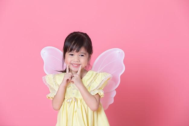 Doce menina vestida com asas de anjo e sorriso na parede rosa.
